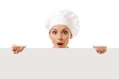 Cozinheiro da mulher que olha sobre o quadro de avisos de papel do sinal. Imagens de Stock Royalty Free