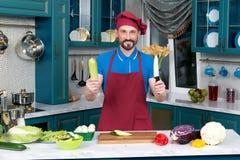 Cozinheiro de sorriso com faca e zuccini verde nas mãos Arma principal do ` s do homem na cozinha imagem de stock royalty free
