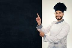 cozinheiro de sorriso que aponta no quadro-negro vazio Copie o espaço foto de stock royalty free