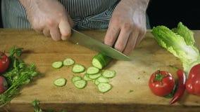 Cozinheiro do cozinheiro chefe que corta profissionalmente um pepino com uma faca do ` s do cozinheiro chefe na placa de corte video estoque