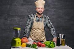 Cozinheiro do cozinheiro chefe que levanta perto da tabela com muitos legumes frescos Imagem de Stock Royalty Free