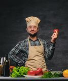 Cozinheiro do cozinheiro chefe que levanta perto da tabela com muitos legumes frescos Fotografia de Stock