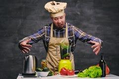 Cozinheiro do cozinheiro chefe que levanta perto da tabela com muitos legumes frescos Foto de Stock