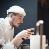 Cozinheiro do cozinheiro chefe do restaurante que guarda o telefone celular fotografia de stock