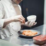Cozinheiro do cozinheiro chefe do restaurante que prepara a faixa salmon e que crambling a salada nos peixes fotos de stock royalty free
