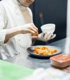 Cozinheiro do cozinheiro chefe do restaurante que prepara a faixa salmon e que salga a fotos de stock
