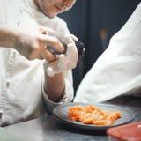 Cozinheiro do cozinheiro chefe do restaurante que prepara a faixa salmon e que salpica a imagens de stock