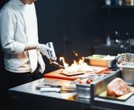 Cozinheiro do cozinheiro chefe do restaurante que prepara o flambe da faixa dos salmões na cozinha aberta fotos de stock