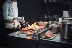 Cozinheiro do cozinheiro chefe do restaurante que prepara o flambe salmon da faixa imagem de stock royalty free