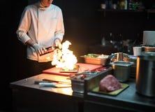 Cozinheiro do cozinheiro chefe do restaurante que prepara o flambe salmon da faixa fotos de stock royalty free