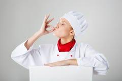 Cozinheiro do cozinheiro chefe da mulher que faz o gesto aprovado com suas mãos após a refeição saboroso Foto de Stock Royalty Free
