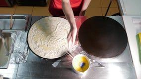 Cozinheiro do cozinheiro chefe da mulher uma panqueca na cozinha na chapa para assar profissional durante a fritada O processo de vídeos de arquivo