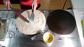 Cozinheiro do cozinheiro chefe da mulher uma panqueca na cozinha na chapa para assar profissional durante a fritada O processo de filme
