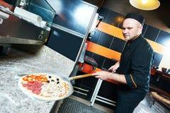 Cozinheiro do padeiro do cozinheiro chefe que põe a pizza no empurrão fotografia de stock royalty free