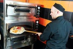 Cozinheiro do padeiro do cozinheiro chefe que põe a pizza no forno fotografia de stock royalty free
