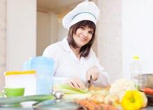 Cozinheiro fêmea com aipo na placa de corte Foto de Stock Royalty Free