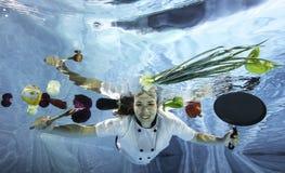 Cozinheiro fêmea novo no uniforme que seleciona os ingredientes para cozinhar debaixo d'água Imagem de Stock Royalty Free