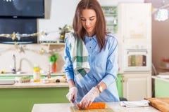 Cozinheiro fêmea que trabalha nas luvas que fazem os rolos de sushi japoneses que cortam os na esteira de bambu que está na cozin Imagem de Stock Royalty Free