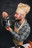 Cozinheiro farpado do cozinheiro chefe que prova a sopa de uma bandeja Fotos de Stock Royalty Free