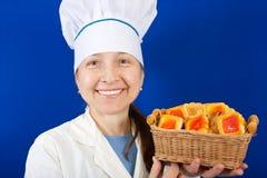 Cozinheiro fêmea com o bolinho sobre o azul Imagem de Stock Royalty Free