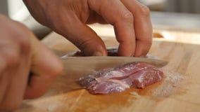 Cozinheiro Hands Cut Meat do close up com a faca na mesa de cozinha filme