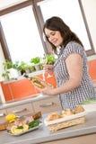 Cozinheiro - mais a mulher do tamanho prepare peixes com vinho Fotos de Stock