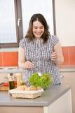 Cozinheiro - mais a mulher feliz do tamanho que prepara a salada foto de stock