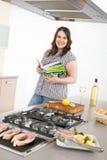 Cozinheiro - mais peixes da grade da mulher do tamanho na cozinha imagem de stock
