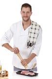Cozinheiro masculino caucasiano novo com, preparando o bife fotos de stock royalty free
