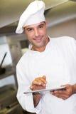 Cozinheiro masculino de sorriso que usa a tabuleta digital na cozinha Foto de Stock