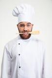 Cozinheiro masculino do cozinheiro chefe que guarda a colher nos dentes Fotografia de Stock Royalty Free