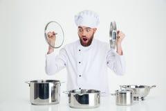 Cozinheiro masculino do cozinheiro chefe que senta-se na tabela com pratos Imagens de Stock Royalty Free