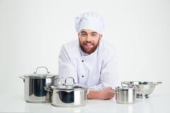 Cozinheiro masculino do cozinheiro chefe que senta-se na tabela com pratos Imagens de Stock