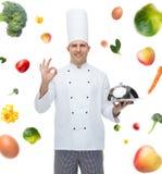 Cozinheiro masculino feliz do cozinheiro chefe com a campânula que mostra o sinal aprovado Imagem de Stock Royalty Free