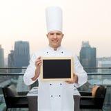 Cozinheiro masculino feliz do cozinheiro chefe que guarda a placa vazia do menu Fotografia de Stock Royalty Free