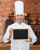 Cozinheiro masculino feliz do cozinheiro chefe que guarda a placa vazia do menu Foto de Stock Royalty Free