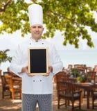 Cozinheiro masculino feliz do cozinheiro chefe que guarda a placa vazia do menu Imagem de Stock
