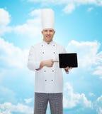 Cozinheiro masculino feliz do cozinheiro chefe que mostra o PC da tabuleta Fotografia de Stock
