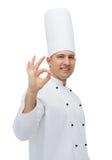 Cozinheiro masculino feliz do cozinheiro chefe que mostra o sinal aprovado Fotos de Stock Royalty Free