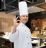 Cozinheiro masculino feliz do cozinheiro chefe que mostra o sinal aprovado Fotografia de Stock Royalty Free