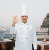 Cozinheiro masculino feliz do cozinheiro chefe que mostra o sinal aprovado Fotografia de Stock