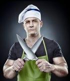 Cozinheiro menacing do homem que guarda duas facas afiadas Imagens de Stock Royalty Free