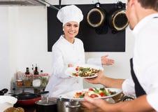 Cozinheiro positivo da mulher que dá a salada à empregada de mesa fotos de stock royalty free