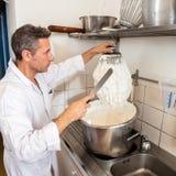 Cozinheiro profissional masculino que limpa o batedor de ovos grande de chicotear os ovos brancos Fotos de Stock Royalty Free