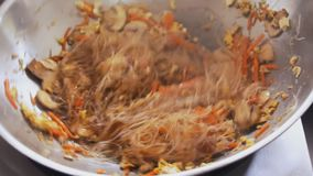 Cozinheiro profissional que frita macarronetes e vegetais no festival do alimento da rua Processo de cozinhar o fim acima filme