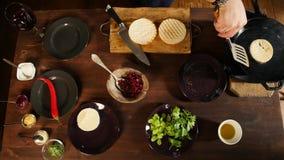 Cozinheiro que adiciona a alface no hamburguer Metragem conservada em estoque Preparando o hamburguer M?os do cozinheiro que prep video estoque