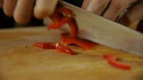 Cozinheiro que corta a pimenta de sino vermelha video estoque