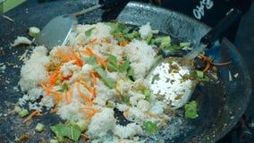 Cozinheiro que frita vegetais e arroz video estoque