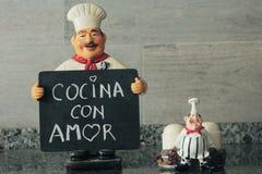 Cozinheiro s?bio com quadro-negro ? disposi??o que diz a cozinha com amor fotos de stock royalty free