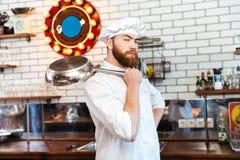 Cozinheiro sério do cozinheiro chefe que está e que guarda a frigideira Foto de Stock Royalty Free